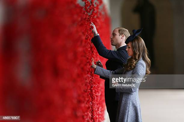 Britain's Prince William and his wife Catherine attach poppies to the Roll of Honour: a long series of bronze panels recording the names of over...