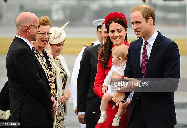 Britain's Prince William and his wife Catherine holding baby Prince George are greeted by Wellington Mayor Celia WadeBrown and her husband Alastair...