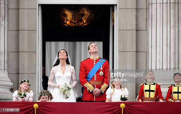 Britain's Prince William and his wife Kate Duchess of Cambridge look up as the Royal Air Force perform a flypast while they stand on the balcony of...