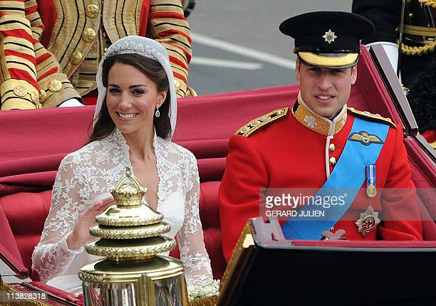 Britain's Prince William and his wife Kate, Duchess of Cambridge, wave as they travel in the 1902 State Landau carriage along the Processional Route...