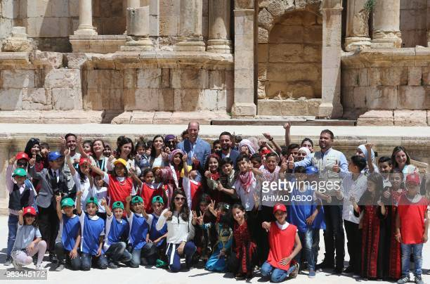 Britain's Prince William and Jordanian Crown Prince Hussein bin Abdullah pose for a group picture with Syrian and Jordanian school children during...