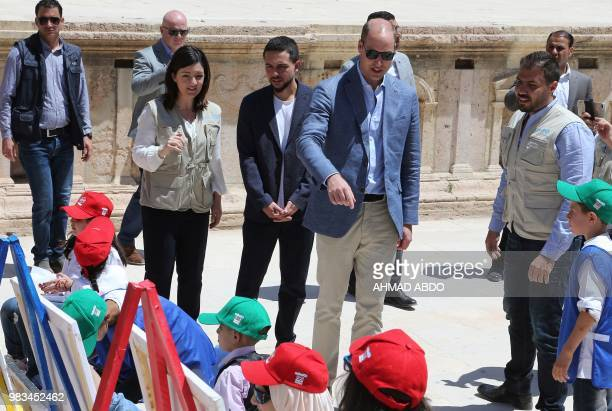 Britain's Prince William and Jordanian Crown Prince Hussein bin Abdullah watch with Syrian and Jordanian school children paint during their visit to...