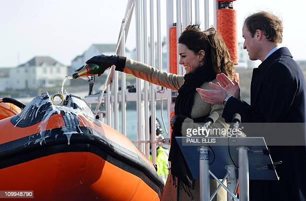 Britain's Prince William applauds while fiancee Kate Middleton pours champagne over a lifeboat at the RNLI Lifeboat Station in Anglesey near Bangor...
