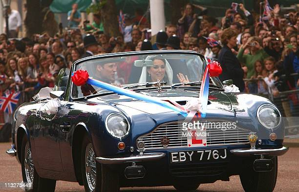Britain's Prince William drives his wife Kate Duchess of Cambridge on The Mall in London in his father Prince Charles' Aston Martin Volante sports...