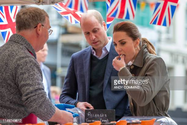 Britain's Prince William Duke of Cambridge and Britain's Catherine Duchess of Cambridge inspect local produce during a visit to the market town of...
