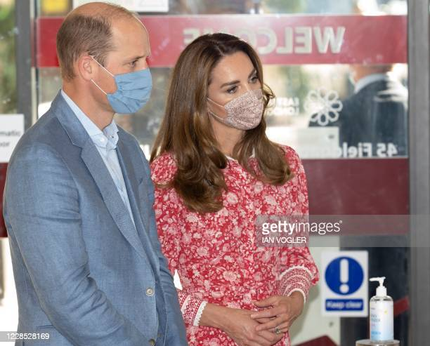 Britain's Prince William, Duke of Cambridge and Britain's Catherine, Duchess of Cambridge wearing face coverings due to the COVID-19 pandemic, react...