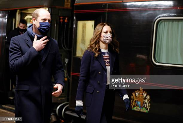 Britain's Prince William, Duke of Cambridge and Britain's Catherine, Duchess of Cambridge disembark the Royal train as they arrive at Manchester...