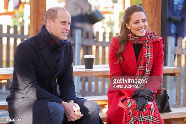 Britain's Prince William, Duke of Cambridge and Britain's Catherine, Duchess of Cambridge sit in the sunshine during a visit to Cardiff Castle in...
