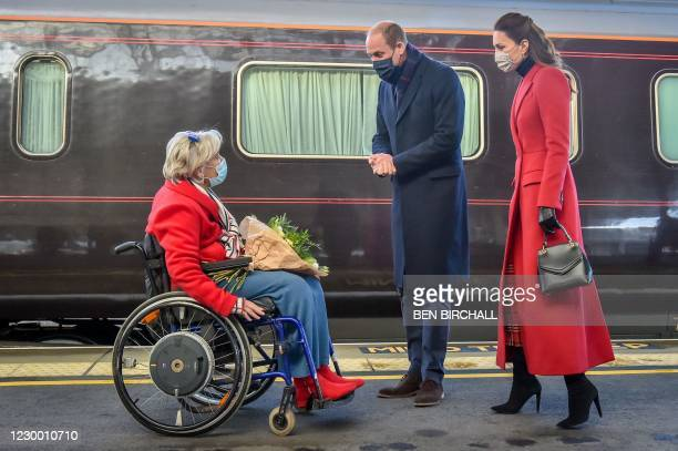 Britain's Prince William, Duke of Cambridge and Britain's Catherine, Duchess of Cambridge wearing protective face coverings to combat the spread of...