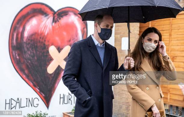 Britain's Prince William, Duke of Cambridge and Britain's Catherine, Duchess of Cambridge, both wearing face coverings due to Covid-19, talk with...
