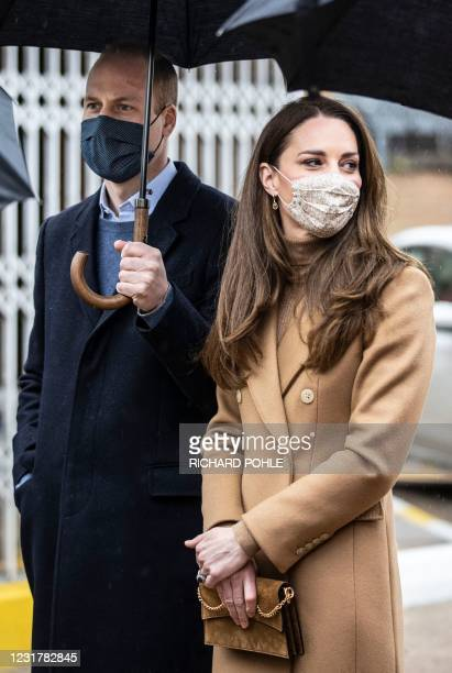 Britain's Prince William, Duke of Cambridge and Britain's Catherine, Duchess of Cambridge both wearing face coverings due to Covid-19, talk with...