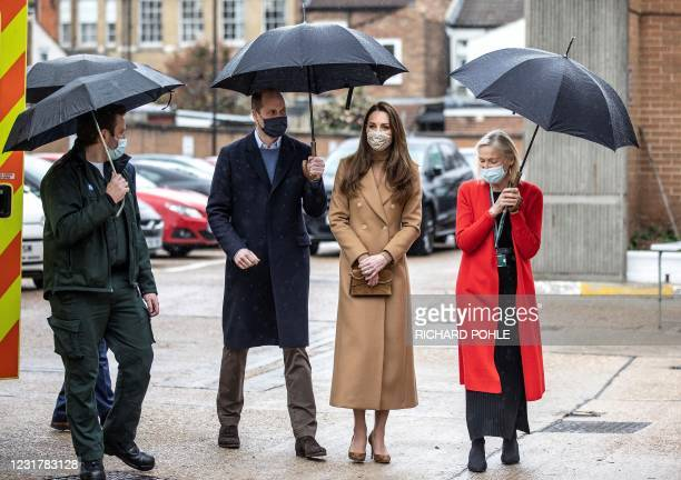 Britain's Prince William, Duke of Cambridge and Britain's Catherine, Duchess of Cambridge , both wearing face coverings due to Covid-19, talk with...