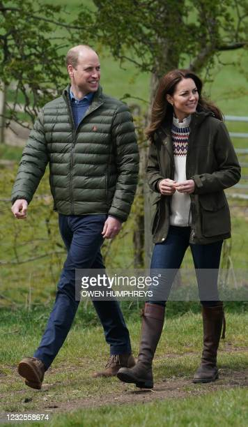 Britain's Prince William, Duke of Cambridge, and Britain's Catherine, Duchess of Cambridge, react during a visit to Manor Farm in Little Stainton,...