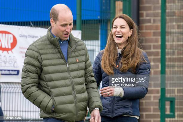 Britain's Prince William, Duke of Cambridge and Britain's Catherine, Duchess of Cambridge gesture during a visit to meet young people supported by...