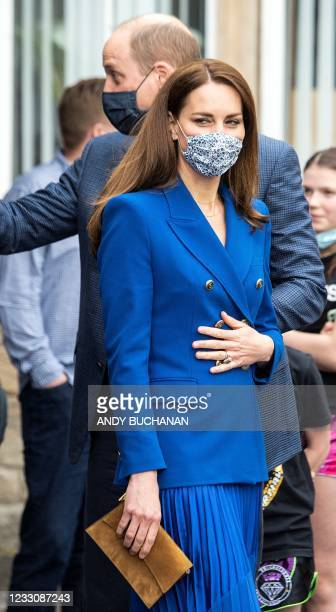 Britain's Prince William, Duke of Cambridge and Britain's Catherine, Duchess of Cambridge, wearing protective face coverings to combat the spread of...
