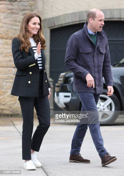 Britain's Prince William, Duke of Cambridge and Britain's Catherine, Duchess of Cambridge gesture during their visit to meet local fishermen and...
