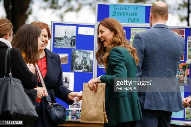 Britain's Prince William, Duke of Cambridge and Britain's Catherine, Duchess of Cambridge gesture during their visit to Starbank Park to hear about...