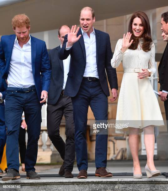 Britain's Prince William Duke of Cambridge and Britain's Catherine Duchess of Cambridge wave as they host with Britain's Prince Harry a Special...
