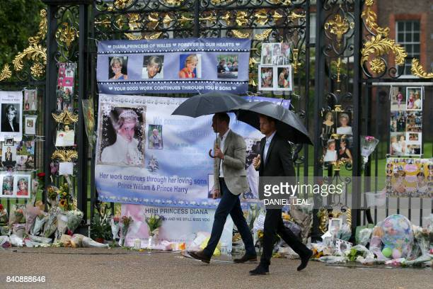 Britain's Prince William Duke of Cambridge and Britain's Prince Harry look at tributes left by members of the public at one of the entrances of...