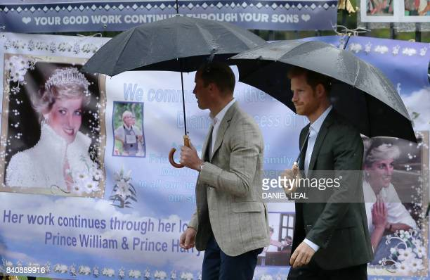TOPSHOT Britain's Prince William Duke of Cambridge and Britain's Prince Harry look at tributes left by members of the public at one of the entrances...