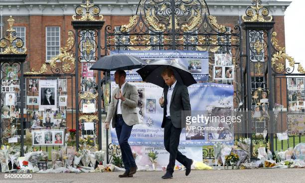 TOPSHOT Britain's Prince William Duke of Cambridge and Britain's Prince Harry walk away after looking at tributes left by members of the public at...