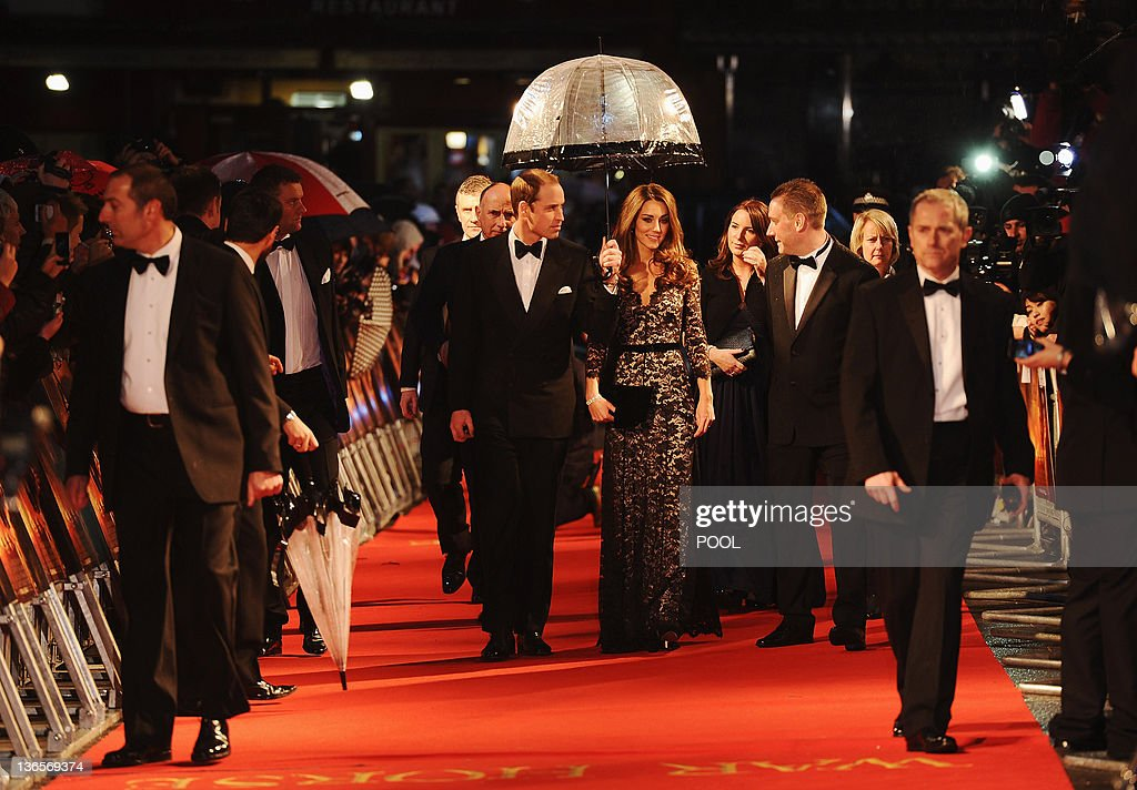 Britain's Prince William (CL), Duke of Cambridge, and Catherine, Duchess of Cambridge (CR), walk down the red carpet with an umbrella as they attend the UK premiere of US director Steven Spielberg's 'War Horse' in Leicester Square central London on January 8, 2012. Michael Morpurgo's book was turned into a hugely successful international theatrical hit before being made into a film. Starring British actor Jeremy Irvine, the film tells the story of the First World War through the journey of a horse and it's owner.