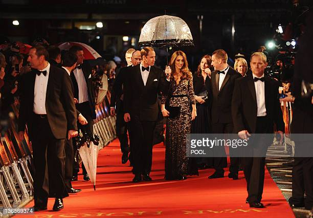 Britain's Prince William , Duke of Cambridge, and Catherine, Duchess of Cambridge , walk down the red carpet with an umbrella as they attend the UK...