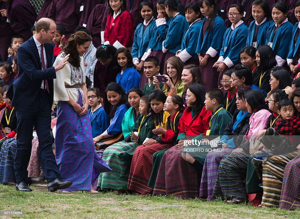 Britain's Prince William (L), Duke of Cambridge, and Catherine (2nd L), Duchess of Cambridge, greet local families during an event at the Changlingmethang National Archery ground in Thimphu during a visit to Bhutan on April 14, 2016. / AFP / ROBERTO