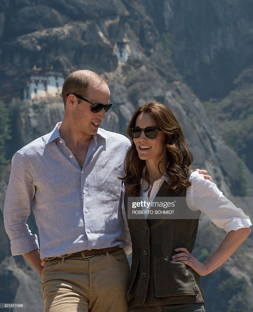 Britain's Prince William (L), Duke of Cambridge, and Catherine, Duchess of Cambridge, pose for a photograph halfway up the trail leading to a Buddhist monastery referred to as the 'Tiger's Nest' (behind) on their two-day visit to Bhutan on April 15, 2016. / AFP / ROBERTO