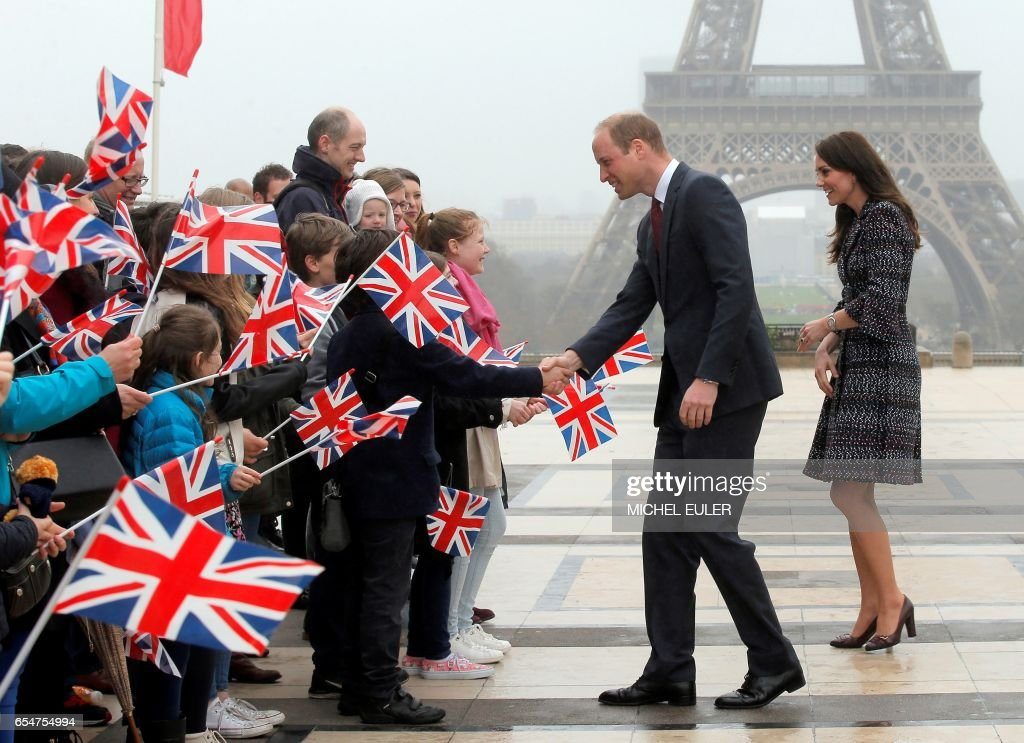TOPSHOT - Britain's Prince William, Duke of Cambridge (L) and his wife Britain's Kate, Duchess of Cambridge (R) meet with people near the Eiffel Tower in Paris on March 18, 2017. Britain's Prince William pledged on the eve that his country will retain close links with France despite Brexit, as he and his wife Kate began a two-day visit to Paris. / AFP PHOTO / POOL / Michel Euler