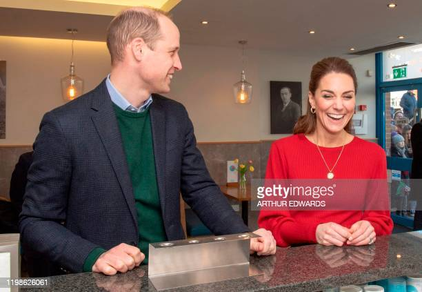 Britain's Prince William Duke of Cambridge and his wife Britain's Catherine Duchess of Cambridge share a joke at the counter during their visit to...