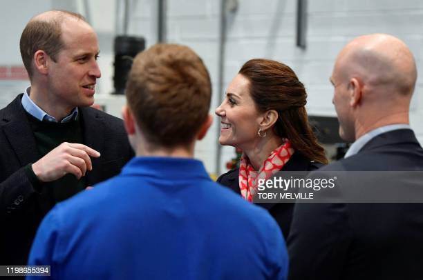 Britain's Prince William Duke of Cambridge and his wife Britain's Catherine Duchess of Cambridge speak to employees at the training centre during...