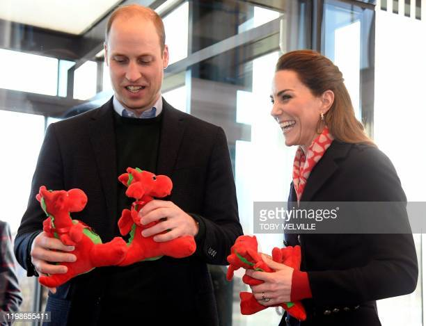Britain's Prince William, Duke of Cambridge and his wife Britain's Catherine, Duchess of Cambridge hold red dragon toys, given to them as gifts for...