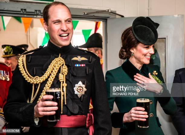 Britain's Prince William Duke of Cambridge and his wife Britain's Catherine Duchess of Cambridge react as they each hold a pint of Guinness whilst...
