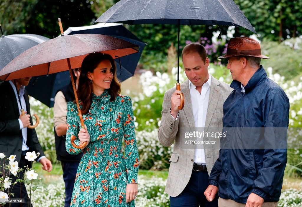 Britain's Prince William, Duke of Cambridge (C), and his wife Britain's Catherine, Duchess of Cambridge (L), shelter from the rain beneath umbrellas as they attend an event at the memorial gardens in Kensington Palace, west London on August 30, 2017. Princes William and Harry prepared to pay tribute to their late mother Princess Diana on Wednesday for the 20th anniversary of her death as wellwishers left candles and flowers outside the gates of her former London residence. The Princes visited the Sunken Garden in the grounds of Kensington Palace, which this year has been transformed into a White Garden, dedicated to their late mother, Britain's Diana, Princess of Wales. / AFP PHOTO / POOL / Kirsty Wigglesworth