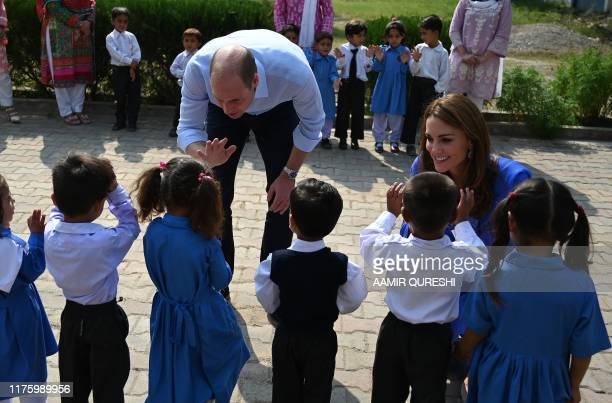 Britain's Prince William , Duke of Cambridge, and his wife Catherine , Duchess of Cambridge, meet with school children during their visit to a...