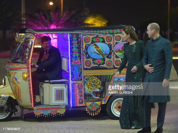 Britain's Prince William Duke of Cambridge and his wife Catherine Duchess of Cambridge look at an autorickshaw driver as they arrive to attend a...