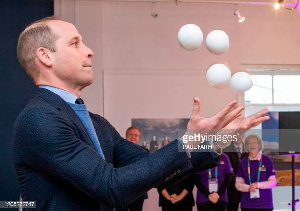 Britain's Prince William, Duke of Cambridge attempts juggling as he attends a special event in Tribeton in Galway, western Ireland, on March 5, 2020...