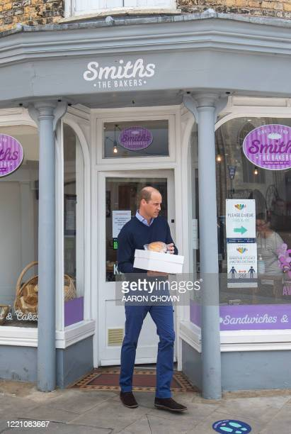 Britain's Prince William, Duke of Cambridge, carries baked goods and pastries as he leaves Smiths the Bakers after a visit in the High Street in...