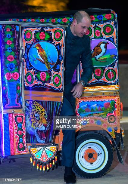 Britain's Prince William Duke of Cambridge comes out from a decorated autorickshaw as he arrives along with his wife Catherine Duchess of Cambridge...