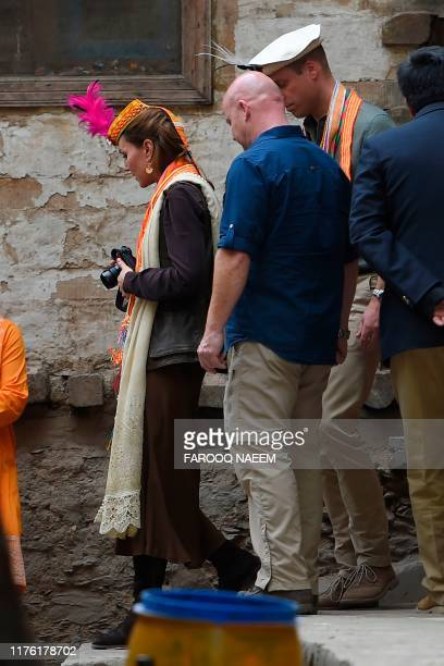 Britain's Prince William , Duke of Cambridge follows his wife Britain's Catherine , Duchess of Cambridge, as she holds a camera during their visits...