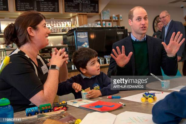 Britain's Prince William Duke of Cambridge gestures as he meets with local parents and carers during his visit with his wife Britain's Catherine...