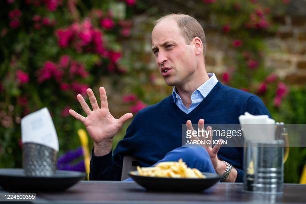 Britain's Prince William, Duke of Cambridge, gestures as he talks to the landlords and workers at The Rose and Crown pub in Snettisham in eastern...