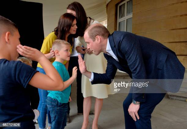 Britain's Prince William Duke of Cambridge greets a family backstage during a Special Garden Party at Buckingham Palace in central London on May 13...