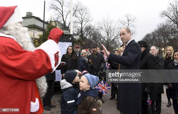 Britain's Prince William Duke of Cambridge greets a person dressed up as Santa Claus as he visits the Esplanade Park and the Manta's Market winter...