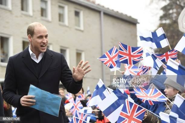 Britain's Prince William Duke of Cambridge greets pupils during a visit at Lauttasaari primary school in Helsinki Finland on November 30 2017 The...