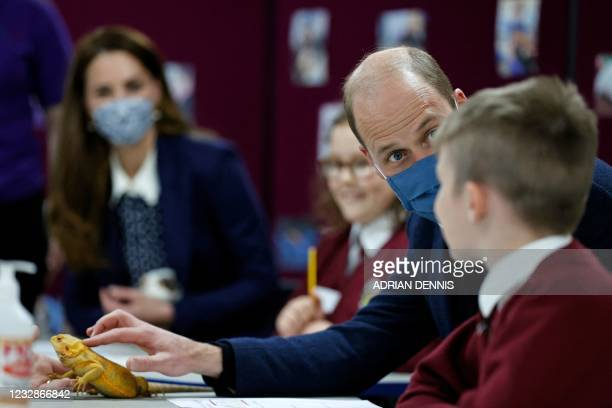 Britain's Prince William, Duke of Cambridge, handles a chameleon as he joins a group of local school children from Loxdale Primary School during a...