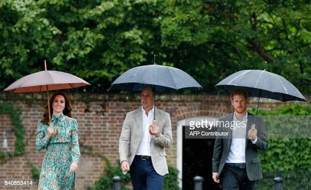 TOPSHOT Britain's Prince William Duke of Cambridge his wife Britain's Catherine Duchess of Cambridge and his brother Britain's Prince Harry shelter...