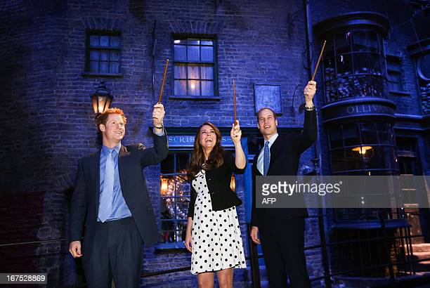 Britain's Prince William Duke of Cambridge his wife Catherine Duchess of Cambridge and brother Prince Harry raise their wands on the set used to...