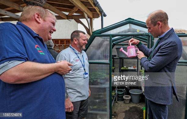 Britain's Prince William, Duke of Cambridge holds a pink watering can during his visit to Brighter Futures, a consortium of eight local groups which...
